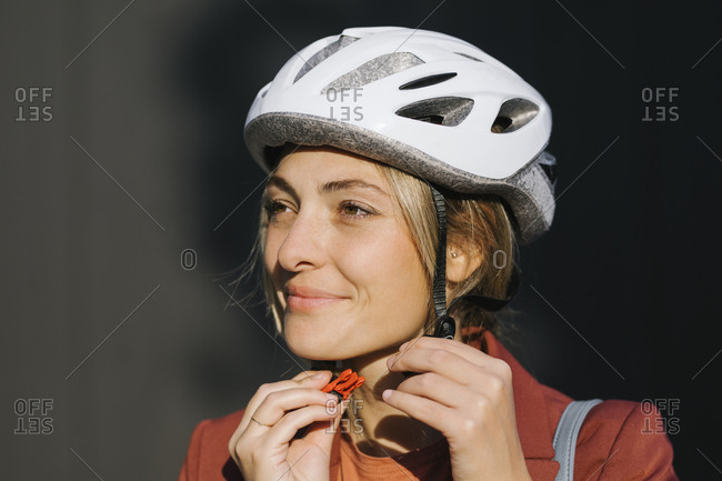 Beautiful young Caucasian woman putting safety driving helmet on her head.