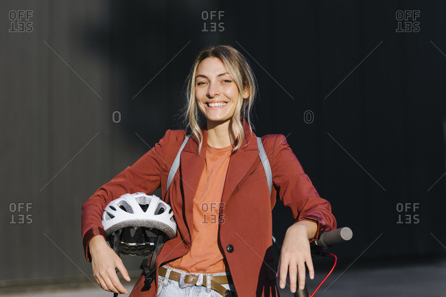 Portrait of pretty confident woman holding a helmet and electrical scooter and looking at camera.