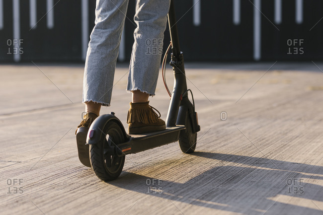 Legs of unrecognizable casual woman driving electrical scooter.
