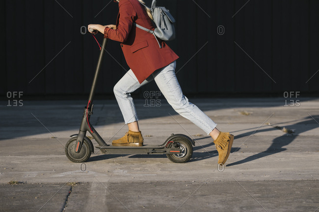 Anonymous woman in jeans driving electrical scooter.