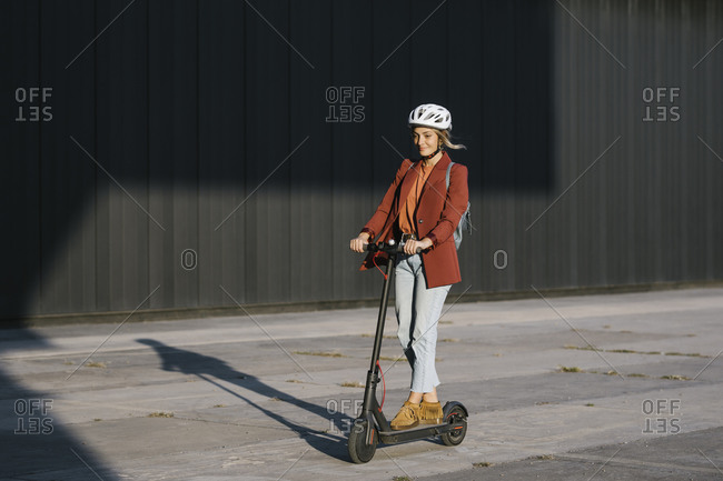 Young beautiful businesswoman with safety helmet on her head driving electrical scooter.