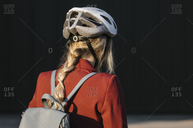 Back view of young woman wearing safety driving helmet.