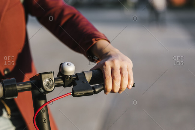 Hands of anonymous woman driving electrical scooter.