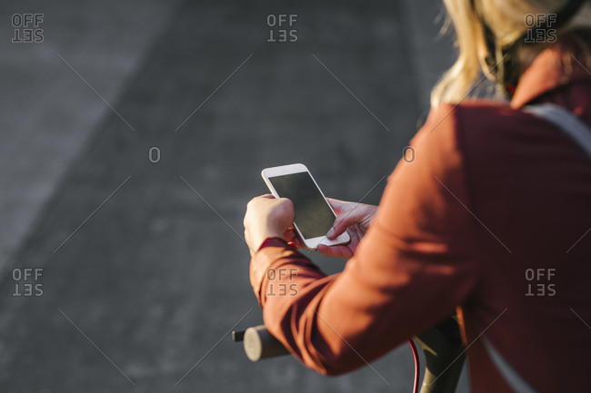 Hands of anonymous woman standing on an electrical scooter and holding her cell phone.
