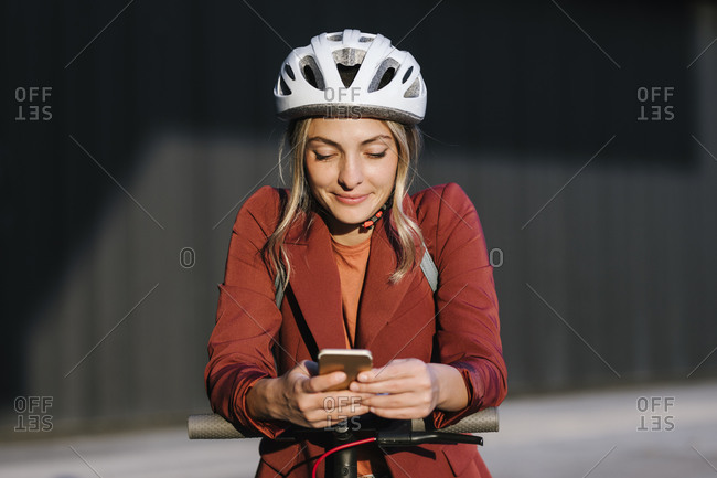 Pretty confident woman with a safety driving helmet and electrical scooter typing on her cell phone.