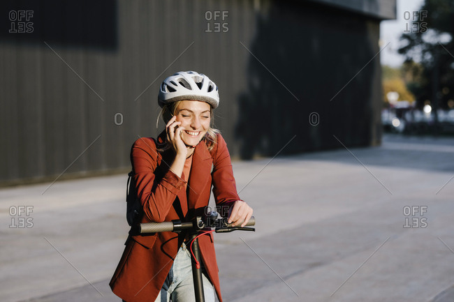 Pretty smiling young woman standing on electrical scooter and talking on her cell phone.
