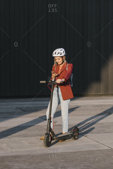Young beautiful businesswoman with safety helmet on her head holding electrical scooter and typing on a cell phone.
