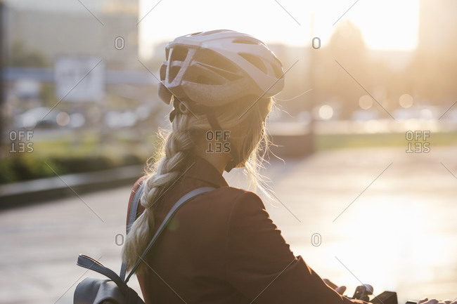 Young businesswoman standing on sunset with safety helmet for scooter driving.