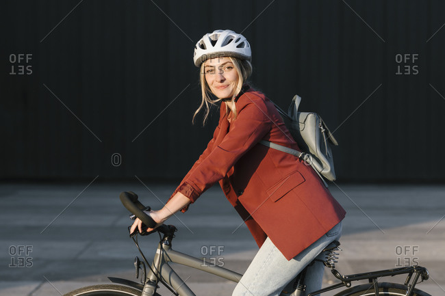 Portrait of beautiful smiling young woman riding a bike and looking at camera.