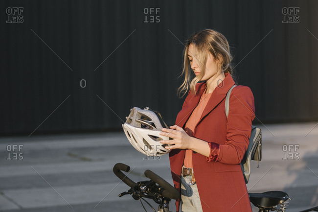 Beautiful young woman putting a helmet on her head for safety bicycle riding.