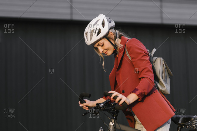 Beautiful young businesswoman with a helmet on her head riding a bicycle.