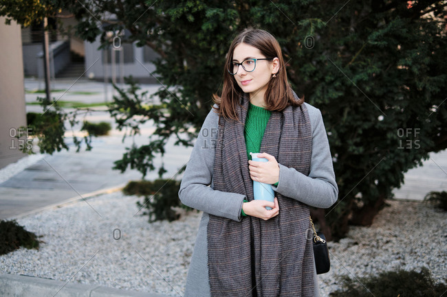 Young woman wearing a grey coat in an urban location with vacuum flask in her hands