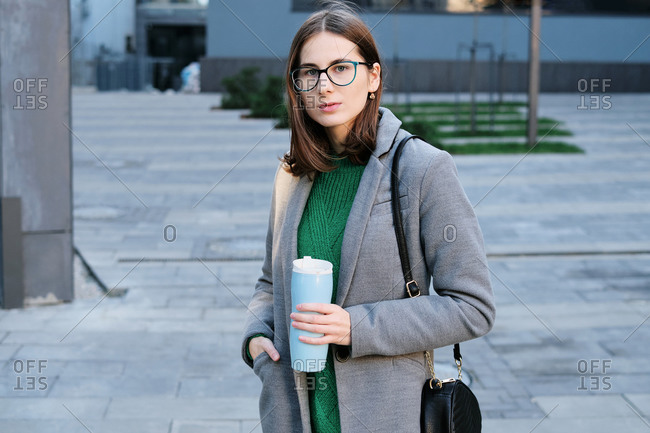 Attractive woman wearing a grey coat in an urban location with vacuum flask in her hands