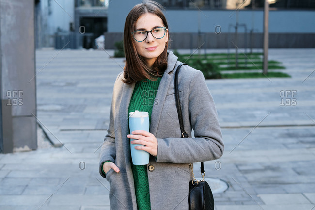 Attractive young woman wearing a grey coat in an urban location with vacuum flask in her hands