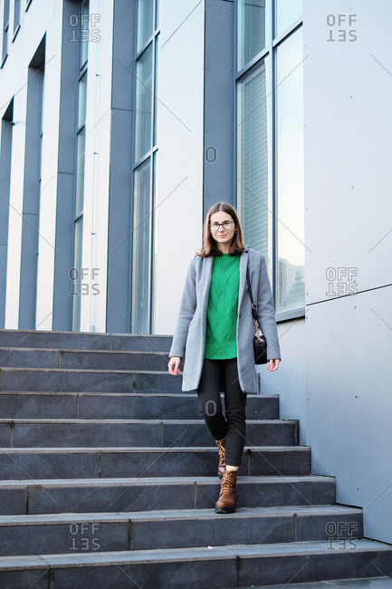 Young beautiful woman wearing a grey coat standing on steps of urban building