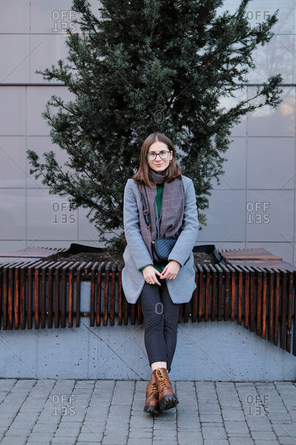 Young woman wearing a grey coat sitting on urban bench