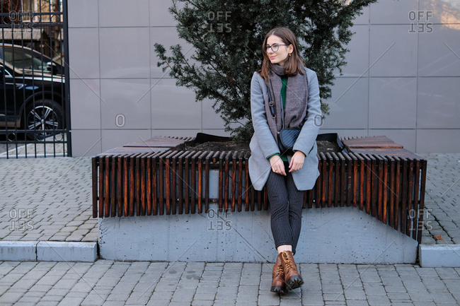 Attractive young woman wearing a grey coat sitting on urban bench