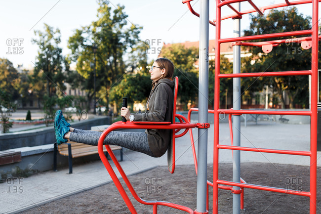 Young woman doing leg lefts on outdoor gym equipment