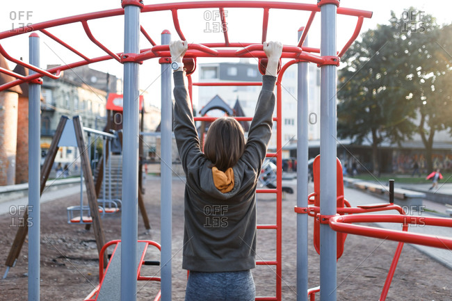Woman doing chin-ups on outdoor gym equipment