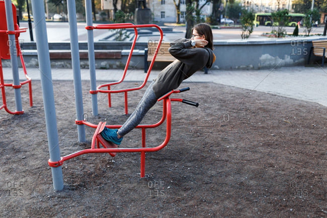 Young woman doing exercises on outdoor gym equipment