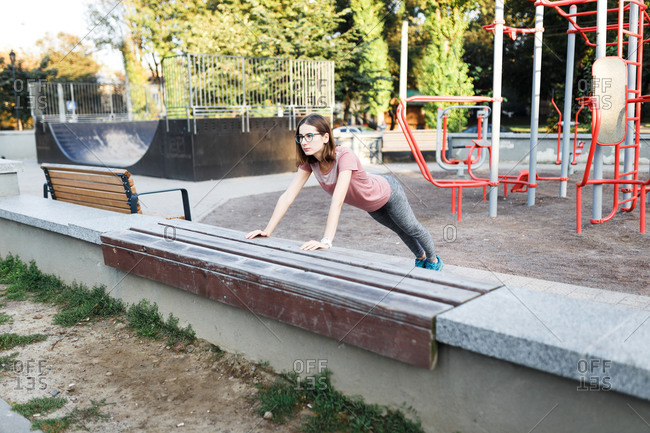 Young woman doing pushups at an outdoor gym park