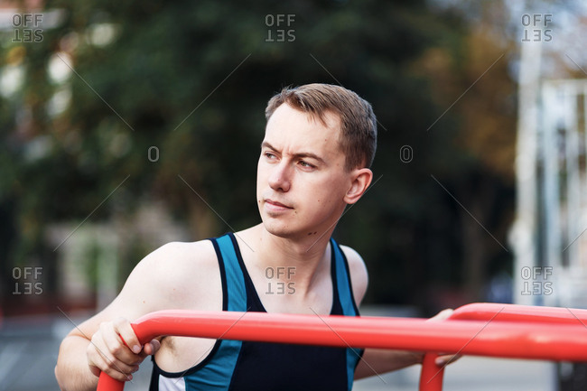 Young man using training apparatus at an outdoor gym park
