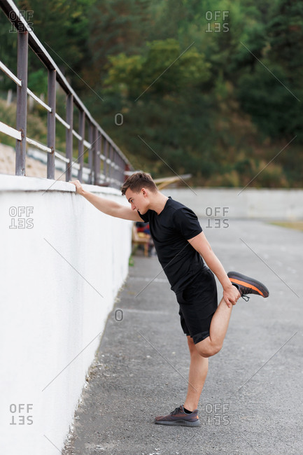 Active young man at a sport stadium leaning on wall doing stretches