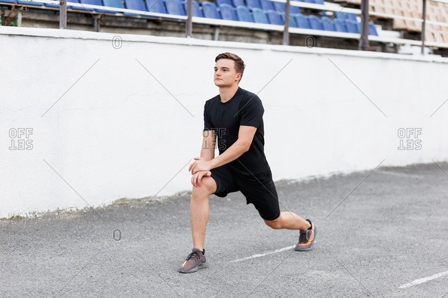 Active young man at a sport stadium doing lunges during workout
