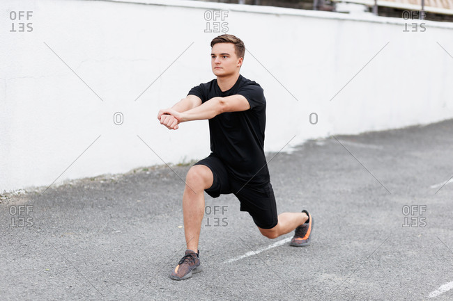 Young man at a sport stadium doing lunges and stretching his arms during workout