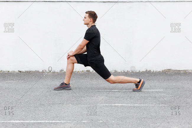 Active young man at a sport stadium doing lunges before workout