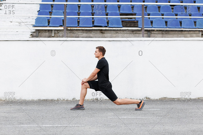 Young man at a sport stadium doing lunges before workout