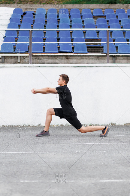 Active young man at a sport stadium doing lunges and stretching his arms during workout