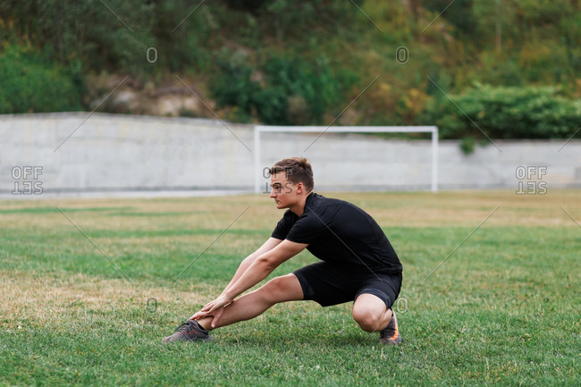 Active young man doing yoga on a sport stadium field