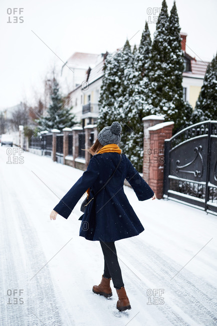 Rear view of young woman wearing a blue coat and yellow scarf on a snowy winter street