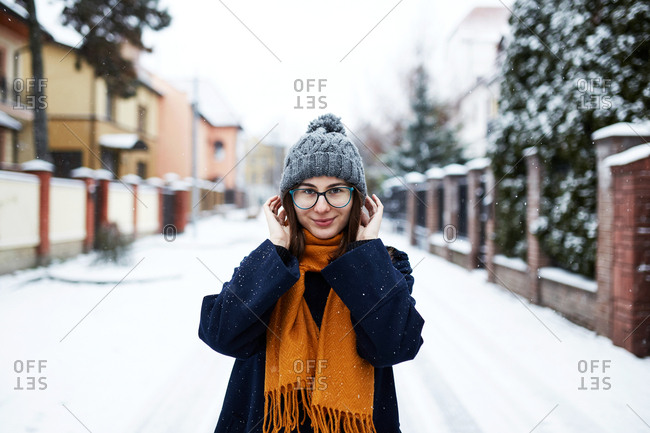 Portrait of a young beautiful woman wearing a blue coat and yellow scarf on a snowy winter street