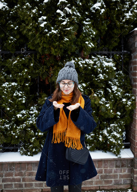 Stylish woman on a snowy winter street catching snowflakes in her hands