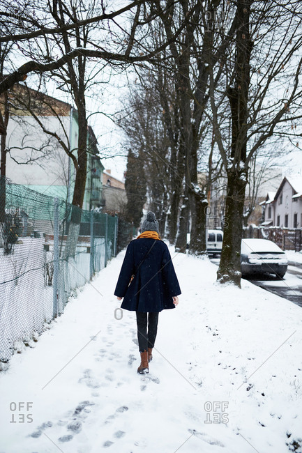 Rear view of young woman wearing a blue coat and yellow scarf walking on a snowy winter street