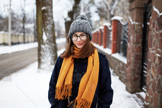 A young beautiful woman wearing a blue coat and yellow scarf on a snowy street in winter