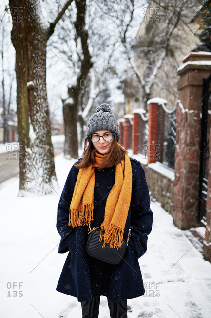 Portrait of a young beautiful woman wearing a blue coat and yellow scarf on a snowy street in winter