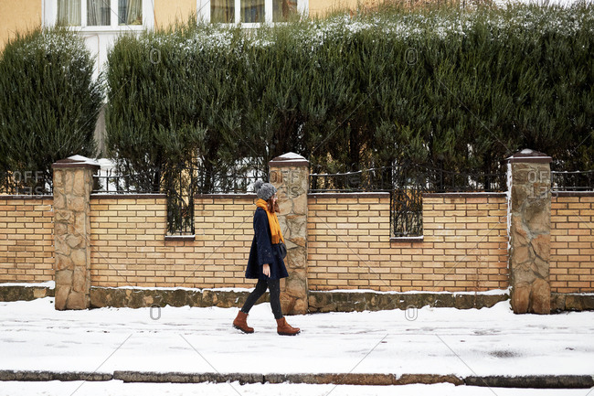 Young woman wearing a blue coat and yellow scarf walking on a snowy winter street