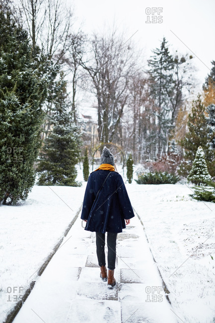 Rear view of young woman wearing a blue coat and yellow scarf walking at snowy park in winter