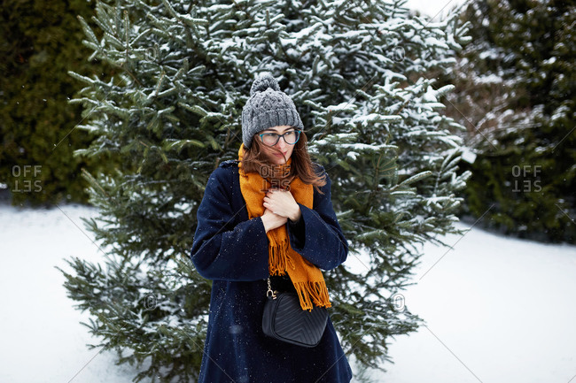Stylish young woman shivering beside snow covered tree at a park
