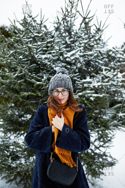 Stylish young woman shivering by a snow covered tree at a park