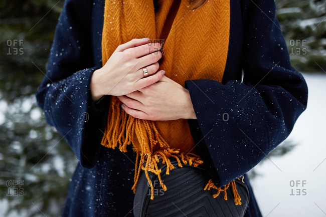 Close up of a stylish young woman shivering in a snowy park in winter