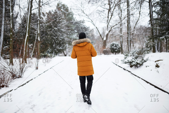 Rear view of young man wearing a yellow coat walking at snowy park in winter