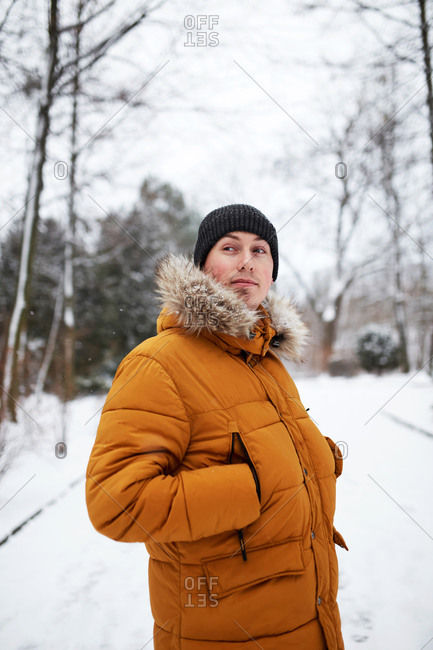 Handsome young man wearing a yellow coat at snowy park in winter