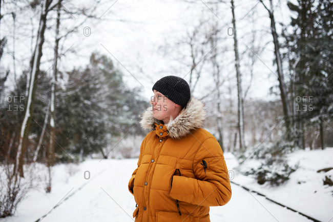 Handsome young man with his hands inside his yellow coat at snowy park in winter
