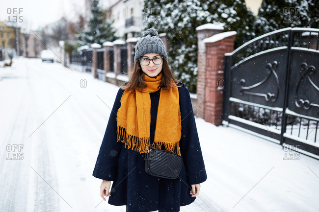 Young beautiful woman wearing a blue coat and yellow scarf on a snowy winter street