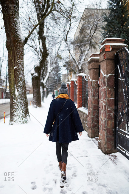Back view of young woman wearing a blue coat and yellow scarf walking on a snowy winter street