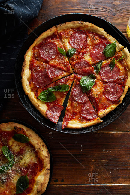 Rustic pizza pepperoni with basil on wooden table